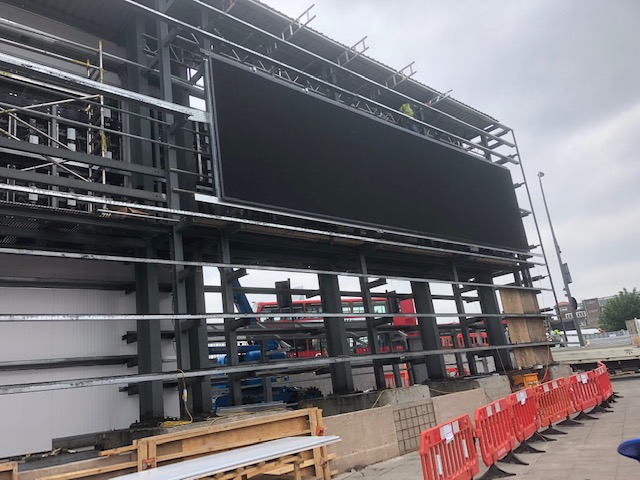 Scaffolding to install a screen on the façade of a facility